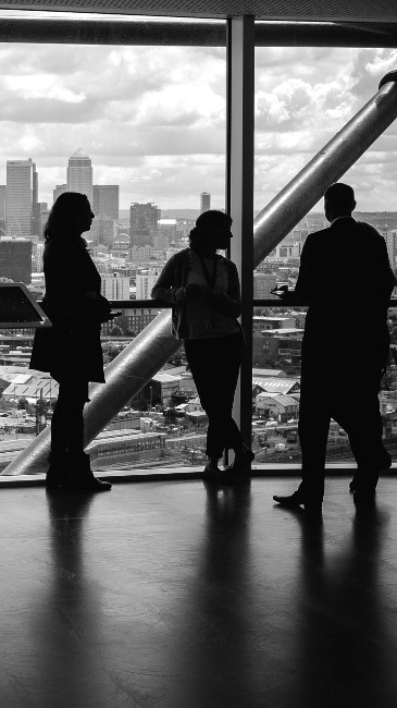 A group of people having a conversation in an office building overlooking Canary Wharf in London, UK
